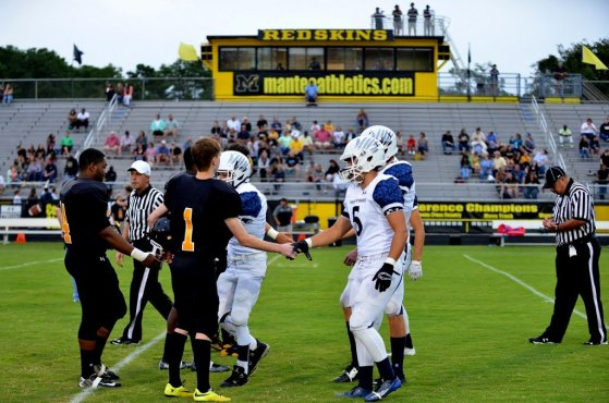 First Flight and Manteo captains meet mid field before the teams hit the field during the Marlin Bowl in Manteo Monday night.